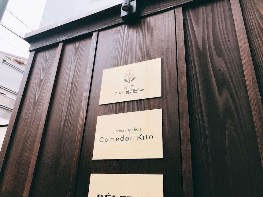 喫茶ニューポピーの金色背景に黒色で文字が書かれたお店の看板